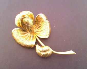 gold coloured flower brooch