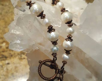 AA quality freshwater pearls accented with copper spacers and toggle. Bracelet 8 inches overall length.