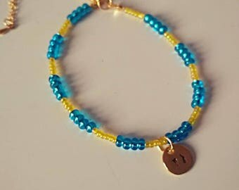 Yellow blue beaded bracelet with PJ tag