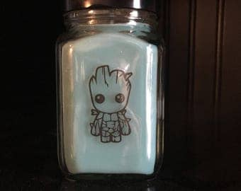 Baby Groot inspired Fandom Candle in New Growth Scent. A blend of Fresh cut grass, Avacado, Sea Salt, and Sage.