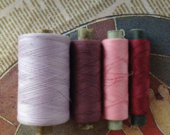 Spools of threads set. Vintage organic cotton 4 threads spools in pink-purple colors.