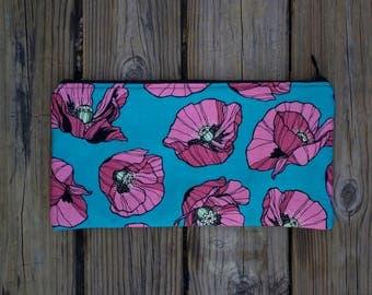 cotton pink poppy clutch on green background