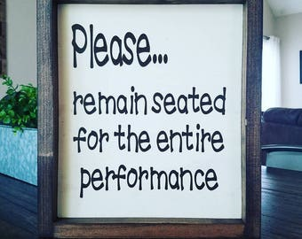 Please remain seated for the entire performance bathroom sign