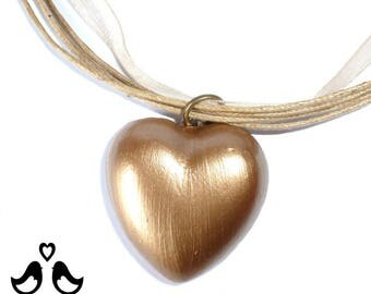 Golden heart pendant on a gold organza ribbon necklace