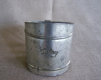 Vintage flour sifter with hand squeezed handle.