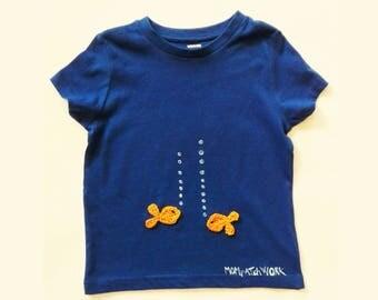 blue t-shirt with crochet application. orange minnow