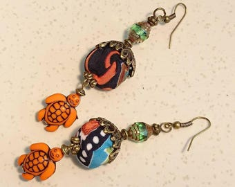 "Earrings ""Colombo"" PomPoms satin fabric, ""turtle"" charms, Czech glass beads and Tibetan style antique bronze findings."