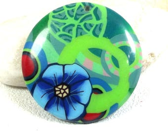 Green cabochon: a blue flower stylized on a background of circles. Hand made.