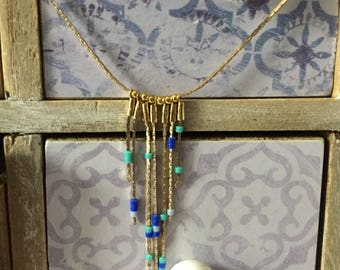 The necklace gold and these blue beads