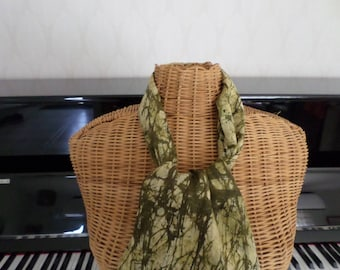 scarf in shades of green with a design that looks like branches