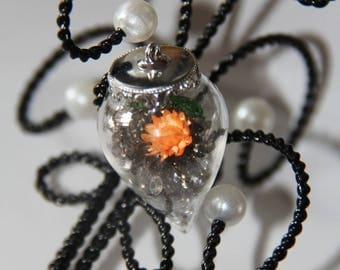 The sharp glass vial filled with Crystal beads gray and a small flower orange