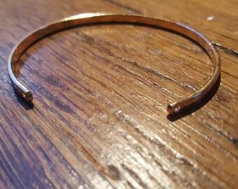 The flat gold colored metal Bangle bracelet