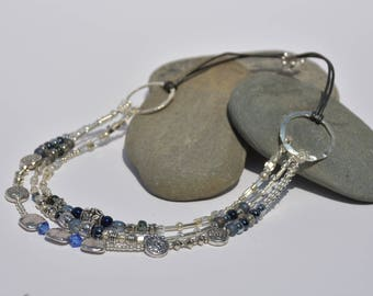 Glass, metal and crystal beaded necklace on leather necklace with hues of grey blue and silver
