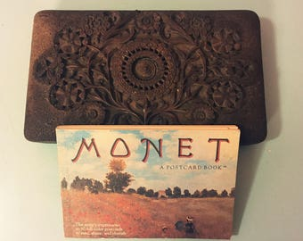Wood carved box with a collection of Monet post cards.