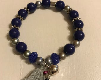 Purple beaded bracelet with tassel charm