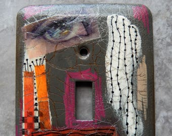 Stormy Eyes, switch plate cover, mixed media, dark gray, pink, orange, white, black, one of a kind