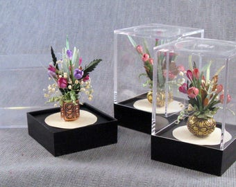 Red tulips arrangement in a pot all inside an acrylic showcase box