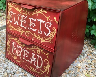 Bread box large double door retro up cycled finished in red with stain overtop and hand painted scroll work and lettering.