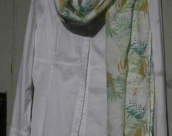 A Large 100% Cotton Scarf on a White background, printed with a lovely leaf design in shades of Green, Mustard and White.