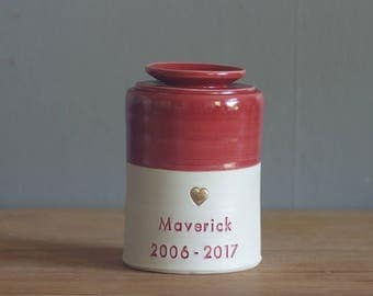 custom urn. gold infilled stamp with ceramic lid, straight shaped urn with heart stamp. modern simple urn for ashes. candy red urn.
