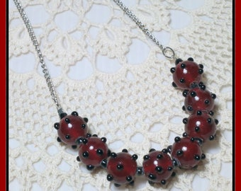 Cherry red glass.  Black Spots.  Lamp-work. Handmade beads.  Silver plated chain. One of a Kind. Teluma Designs.  Mature women.