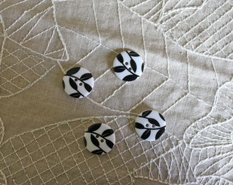 4 plastic buttons with black leaves