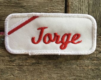 "Jorge. A white work shirt name patch that says ""Jorge"" in red script with white border"
