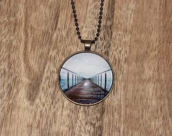 Pendant necklace featuring a photograph of a jetty over water