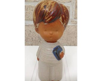 Clay choirboy figurine dressed in white with blue book