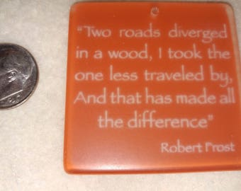 red frosted lucite 1.75 inch pendant with the Robert Frost, A road less traveled poem printed in white on one side