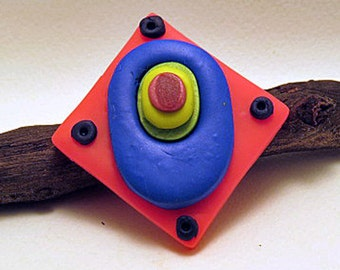 Brooch. Diamond shaped brooch in bright colours and raised levels.