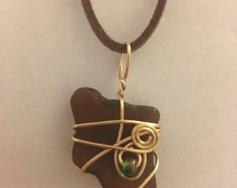 Brown sea glass necklace wrapped in gold wire with green bead