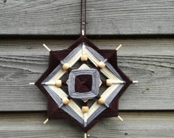 Ojo de Dios (God's eye) wool hanger in the colours beige , brown and grey.