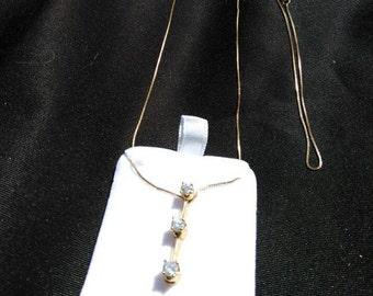 14k yellow gold three stone diamond pendant.