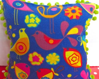 Blue cushion with PomPoms, sewn into fabric with printed birds children