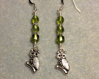 Silver owl charm dangle earrings adorned with olive green Czech glass beads.