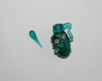 Deep teal with accents of pink flowers and green leaves on this beautiful lampwork piece