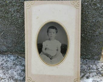 Antique tintype of a young child in a paper frame sleeve