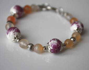 Orange glass, porcelain purple flowers and silver colored metal beads bracelet