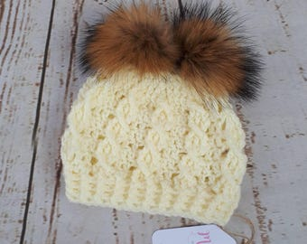 Crochet cable hat in cream with 2 faux fur pom poms age 3-6months