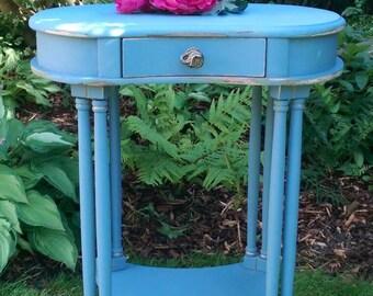 Kidney shaped vintage console table. Dark blue, gold detailing, bronze elephant drawer handle