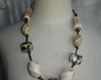 necklace or belt of khaki and ivory beads and brown leather cord