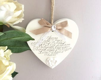 "Fretwork wooden heart painted in white, stamped message ""Love"" and decorated with ceramic heart"