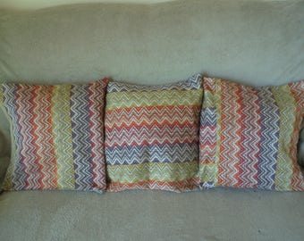 Trio of pillow covers: red, Burgundy, orange, green, purple, plum and gray.