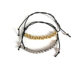 Black elastic strap and gold or silver beads