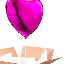 A dark pink heart shaped balloon