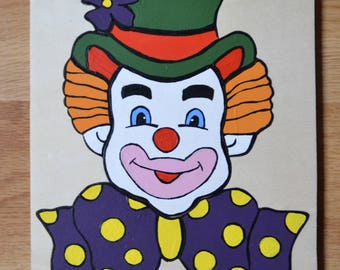 Wooden puzzle of seven pieces representing a clown