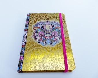multicolored hard cover book and gold 11 x 16, 5 cm arabesque