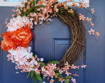 Designer spring and summer floral wreath. Pink, red, white, and peach colored silk flowers with faux greenery. Rustic farmhouse decor