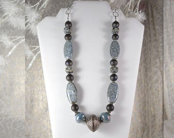 """Ceramic Blue Oval and Cube Beads.  Black Sheen Contrast.  Blue Iridescent Pearls. Silver Sphere Center. 24"""" Long   Lobster Claw Clasp."""
